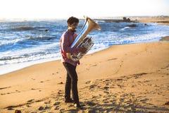 Eenzame musicus die de Tuba op de oceaankust spelen stock afbeelding