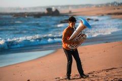 Eenzame musicusinstrumentist die de Tuba op de overzeese kust spelen royalty-vrije stock foto's