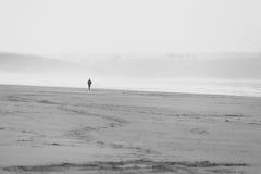 Eenzame persoon die op het strand in de afstand door de mist lopen Stock Afbeeldingen