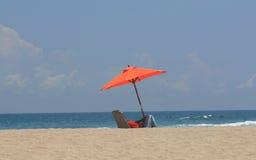 Eenzame persoon op strand onder paraplu Stock Foto's