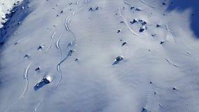 Eenzame professionele skiër die snel bergaf op de mooie sneeuw lege heuvel van het berglandschap in 4k luchthommelmening berijden stock videobeelden