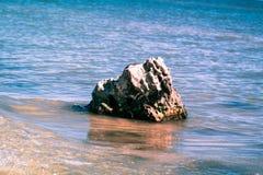 Eenzame rots die van het water uitpuilen Stock Afbeelding