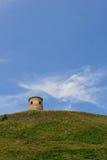 Eenzame steentoren op een groene heuvel Stock Foto