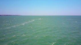 Eenzame surferzeilen op reusachtige oceaan met schuimend spoor stock video