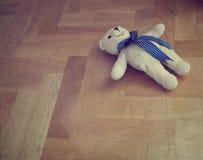 Eenzame teddybeer op de vloer - gestileerd retro stock foto