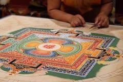 Eenzame Tibetaanse Monnik die aan Mandala werkt Stock Foto