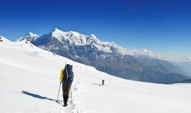 Eenzame trekkers op grote sneeuwfieldsin Himalayagebergte royalty-vrije stock fotografie
