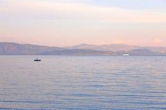 Eenzame visser in Ionische Overzees met Albanese kust op de achtergrond, Ipsos Village, het Eiland van Korfu, Griekenland, Europa royalty-vrije stock foto