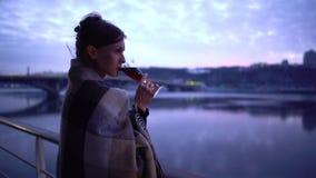 Eenzame vrouw in deken die zich dichtbij de de rivier en het drinken alcohol bevinden stock videobeelden
