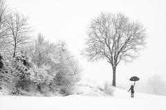 Eenzame vrouw die in sneeuwonweer lopen Stock Foto