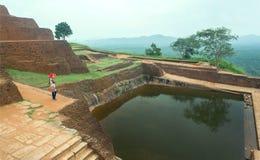 Eenzame vrouw het letten op ruïnes van de oude Sigiriya-stad met waterpool en archeologisch gebied Royalty-vrije Stock Afbeeldingen