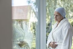 Eenzame vrouw met kanker die zich naast een venster bevinden royalty-vrije stock foto's