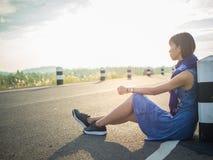 Eenzame vrouwenzitting op de weg Royalty-vrije Stock Afbeelding