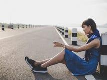 Eenzame vrouwenzitting op de weg Stock Fotografie