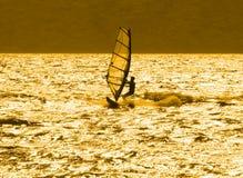 Eenzame windsurfer bij zonsondergang Stock Afbeeldingen