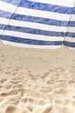 Eenzame witte en blauwe strookparaplu op het strand Stock Foto's