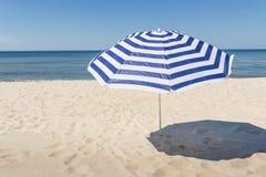 Eenzame witte en blauwe strookparaplu op het strand Stock Foto