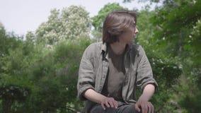 Eenzame zenuwachtige jonge mensenzitting op de bank in het park die op zijn vriend of meisje wachten De kerel die voorbereidingen stock videobeelden