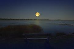 Eenzame zetel naast het meer met volle maan stock afbeeldingen