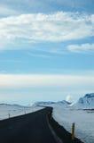 Eenzame zwarte weg, sneeuw, blauwe hemel, IJsland Stock Foto