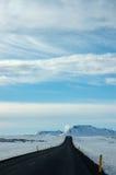 Eenzame zwarte weg, sneeuw, blauwe hemel, IJsland Royalty-vrije Stock Fotografie