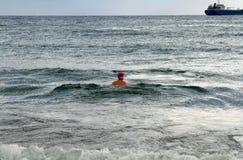 Eenzame zwemmer in een Santa Claus-hoed royalty-vrije stock foto