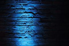 Eerie Blue light on wall background. A blue oblique light from below casts eerie shadows on an old gently curving brick wall royalty free stock photography