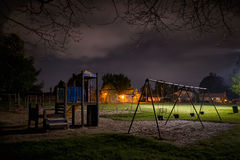 Eerie Children's Playground at Night. A creepy scene of a deserted children's playground in a suburban park at night time Stock Photo