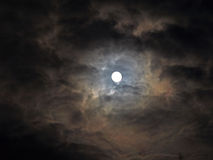 Eerie Clouds with Full Moon. A frightening cloud pattern is lit up by this full moon Stock Photo