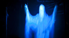Eerie Glowing Ghost. Luminous ghost in flowing white robe appears to be floating against a black background Stock Image