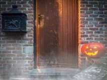 Eerie Halloween Scene. A creepy Halloween scene of a glowing doorway with the eerie shadow of a ghost and a carved, smiling Jack-o-lantern pumpkin on the steps stock photo