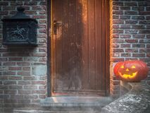 Eerie Halloween Scene. A creepy Halloween scene of a glowing doorway with the eerie shadow of a ghost and a carved, smiling Jack-o-lantern pumpkin on the steps royalty free stock images