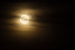 Eerie Moon. An eerie moon masked by thin clouds royalty free stock image