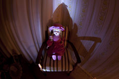 Eerie Possessed Doll. Old doll staring in eerie light Royalty Free Stock Photography