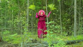 An eerie witch in ritual clothes in the forest performs a ritual dance with the branches of a fern.
