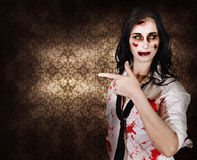 Eerie woman pointing to Halloween copyspace. Terrifying marketing woman promoting dead space when pointing to grunge wallpaper inside a haunted house in a Stock Photo