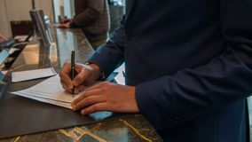 Eerlijke ondernemerschap die bij de ontvangst van het luxehotel registreren stock video