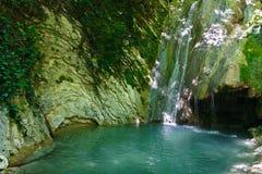 Eerlijke verfrissende waterval onder de rotsen in bergbos Stock Foto's