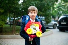 Eerste dag op school, jongen met bloemen stock afbeelding
