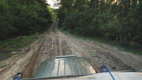 Eerste persoonsmening: Aandrijving langs een modderige landweg in de bossuv-treinen in het hout stock video