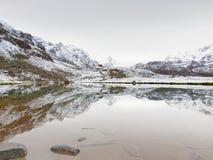Eerste Sneeuw in Bergen De herfstmeer in Alpen met spiegelniveau Nevelige scherpe pieken van hooggebergte Stock Foto