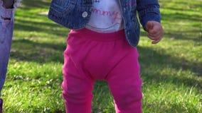 Eerste stappen van babymeisje De babyshand van de moederholding stock video