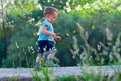 Eerste stappen van leuke babyjongen onder greens royalty-vrije stock afbeelding
