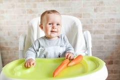 Eerste stevig voedsel voor jong jong geitje Verse organische wortel voor plantaardige lunch De baby eet groenten Gezonde voeding  stock fotografie