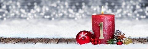 Eerste zondag van komst rode kaars met gouden metaalaantal op houten planken in sneeuwvoorzijde van panorama bokeh achtergrond stock foto's