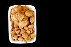 Eet abrikozenpitten in platen, op zwarte grond, Zoete abrikozenzaden Royalty-vrije Stock Fotografie
