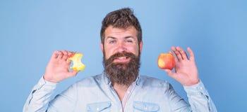 Eet appel elke dag Goede idee van de fruit het gezonde snack altijd Lange baard van mensen houdt de knappe hipster rijpe appel en royalty-vrije stock afbeeldingen
