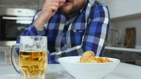 Eet de close-up te zware of vette kerel chips met een mok bier in de keuken Ongezonde levensstijl Een mok van de glaspint van stock video