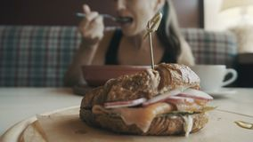 Eet de ontbijt Jonge vrouw in koffie stock footage