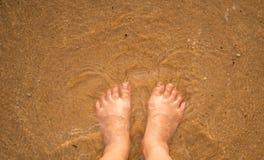 eet del niño pequeño que se coloca solamente en la playa de la arena fotografía de archivo libre de regalías